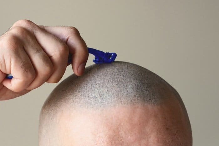 Man Shaving head - choosing razor